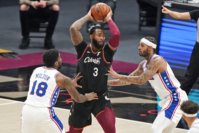 Cleveland Cavaliers' Andre Drummond (3) drives between Philadelphia 76ers' Shake Milton (18) and Mike Scott (1) in the second half of an NBA basketball game, Sunday, Dec. 27, 2020, in Cleveland. The Cavaliers won 118-94. (AP Photo/Tony Dejak)