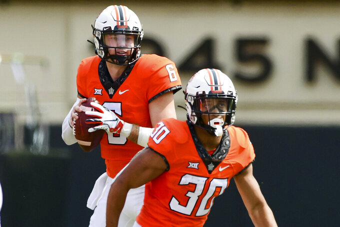Oklahoma State quarterback Ethan Bullock (6) looks past teammate Chuba Hubbard (30) for an open receiver in the first half of an NCAA college football game against Tulsa, Saturday, Sept. 19, 2020, in Stillwater, Okla. (AP Photo/Brody Schmidt)