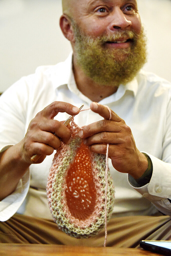 Natchez, Miss., Mayor Darryl Grennell crochets a beanie Thursday, Aug. 22, 2019, in his living room in Natchez, Miss. After learning how to crochet, Grennell started using his new found skill to create beanies for local cancer patients. (Ben Hillyer/The Natchez Democrat via AP)