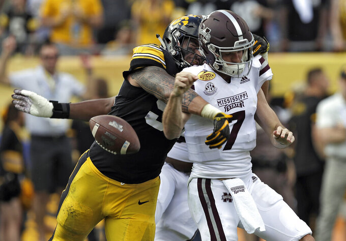 FILE - In this Jan. 1, 2019, file photo, Iowa defensive end A.J. Epenesa (94) strips the ball from Mississippi State quarterback Nick Fitzgerald (7) causing a fumble during the first half of the Outback Bowl NCAA college football game, in Tampa, Fla. Iowa junior A.J. Epenesa knows that he has a strong shot at being picked in the first round of the 2020 NFL Draft should he choose to go pro next spring.  He's just choosing not to think about it until then. Epenesa, a 6-foot-6, 280-pound defensive end who led the Big Ten with 10.5 sacks a year ago despite coming off the bench, is poised for a monster season in 2019. (AP Photo/Chris O'Meara, File)
