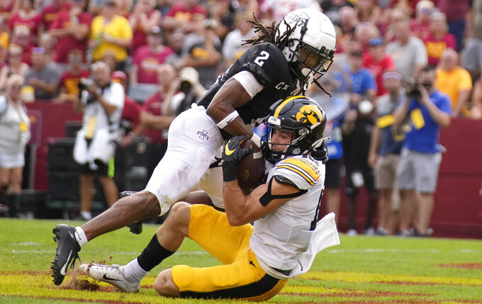 Iowa wide receiver Charlie Jones (16) scores a touchdown despite defensive efforts by Iowa State defensive back Datrone Young (2) during the first half of an NCAA college football game, Saturday, Sept. 11, 2021, in Ames, Iowa. (AP Photo/Matthew Putney)