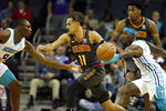 Atlanta Hawks' Trae Young (11) moves the ball past Charlotte Hornets' Terry Rozier (3) and away from Bismack Biyombo (8) during the first half of an NBA basketball game in Charlotte, N.C., Sunday, Dec. 8, 2019. (AP Photo/Bob Leverone)