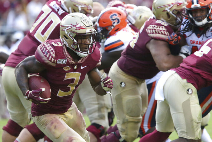 Florida State's Cam Akers, left, looks for an opening in the Syracuse defense during the fourth quarter of an NCAA college football game, Saturday, Oct. 26, 2019, in Tallahassee Fla. (AP Photo/Steve Cannon)
