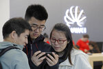 People use a mobile phone in a Huawei retail shop in Shenzhen, China's Guangdong province, Thursday, March 7, 2019. Chinese tech giant Huawei is challenging a U.S. law that labels the company a security risk and would limit its access to the American market for telecom equipment. (AP Photo/Kin Cheung)