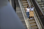 People wear face masks to protect against the coronavirus as they ride an escalator at a retail and office complex in Beijing, Friday, June 5, 2020. China on Friday reported five new confirmed coronavirus cases, all of them brought by Chinese citizens from outside the country. (AP Photo/Mark Schiefelbein)
