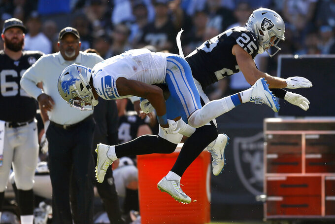 Detroit Lions wide receiver Marvin Jones Jr., left, catches a pass in front of Oakland Raiders free safety Erik Harris (25) during the first half of an NFL football game in Oakland, Calif., Sunday, Nov. 3, 2019. (AP Photo/D. Ross Cameron)
