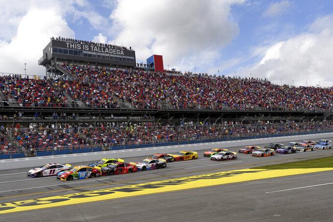 Denny Hamlin (11), and Kyle Busch (18) lead off the start of a NASCAR Cup series auto race Monday, Oct. 4, 2021, in Talladega, Ala. (AP Photo/John Amis)