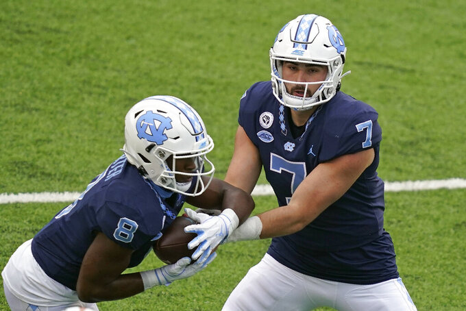 North Carolina quarterback Sam Howell (7) hands off to running back Michael Carter (8) during the first half of an NCAA college football game in Chapel Hill, N.C., Saturday, Oct. 10, 2020. (AP Photo/Gerry Broome)