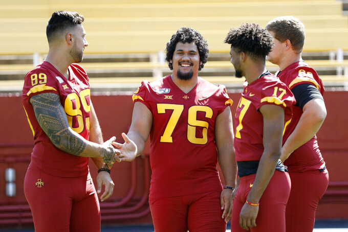 Iowa State nose guard Ray Lima (76) talks with teammates Matt Leo (89) and Darren Wilson (17) during Iowa State's annual NCAA college football media day, Thursday, Aug. 1, 2019, in Ames, Iowa. (AP Photo/Charlie Neibergall)