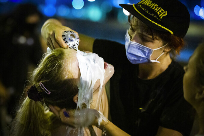 FILE - In this Wednesday, June 3, 2020, file photo, a person pours milk on the face of a protester who was tear-gassed by police officers by the Crescent City Connection in New Orleans, after a viral video of Minneapolis police Officer Derek Chauvin kneeling on George Floyd's neck while he was handcuffed sparked nationwide protests. Nearly a dozen federal lawsuits alleging racist and often abusive tactics by police officers in Louisiana have been filed in the spring of 2021 as part of an initiative by the American Civil Liberties Union of Louisiana called Justice Lab. (Sophia Germer/The Times-Picayune/The New Orleans Advocate via AP, File)