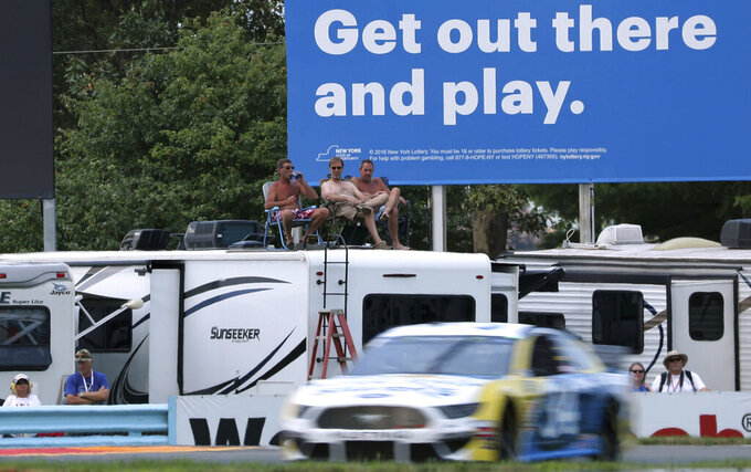 Fans watch the action during a practice run for the NASCAR Cup Series auto race at Watkins Glen International, Saturday, Aug. 3, 2019, in Watkins Glen, New York. (AP Photo/John Munson)