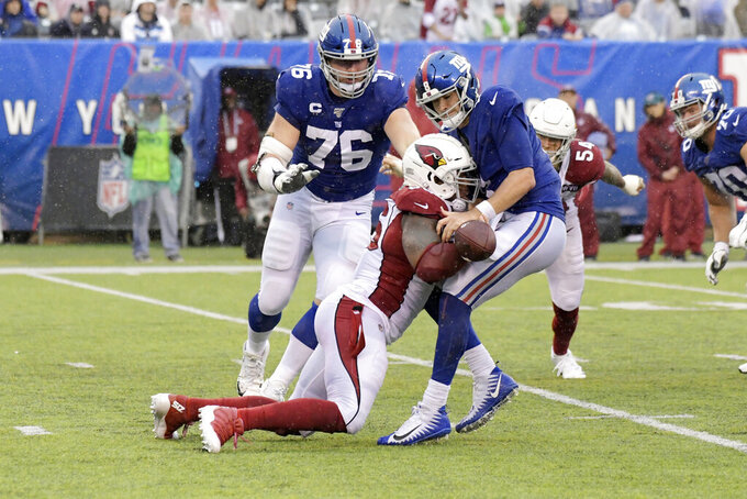 Arizona Cardinals' Terrell Suggs, front left, knocks the ball out of New York Giants quarterback Daniel Jones' hands during the second half of an NFL football game, Sunday, Oct. 20, 2019, in East Rutherford, N.J. (AP Photo/Bill Kostroun)