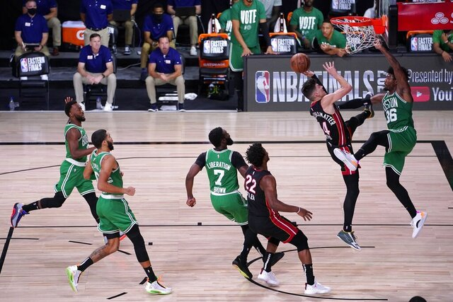 Boston Celtics' Kemba Walker, from left, Jayson Tatum, Jaylen Brown (7), and the Miami Heat's Jimmy Butler (22) look on as Heat guard Tyler Herro (14) attempts to get a shot off against the Celtics' Marcus Smart (36) during the first half of Game 4 of an NBA basketball Eastern Conference final, Wednesday, Sept. 23, 2020, in Lake Buena Vista, Fla. (AP Photo/Mark J. Terrill)