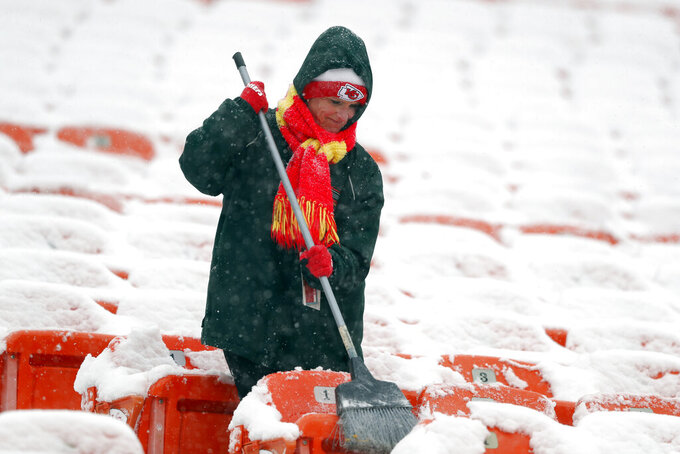 A groundskeeper brushes snow off of seats at Arrowhead Stadium before an NFL divisional football playoff game against the Indianapolis Colts in Kansas City, Mo., Saturday, Jan. 12, 2019. (AP Photo/Charlie Neibergall)