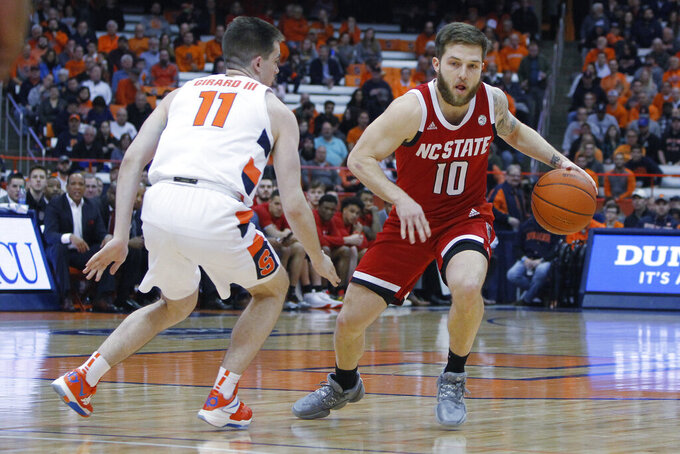 North Carolina State's Braxton Beverly, right, tries to dribble past Syracuse's Joseph Girard III, left, in the first half of an NCAA college basketball game in Syracuse, N.Y., Tuesday, Feb. 11, 2020. (AP Photo/Nick Lisi)