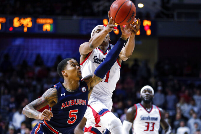 Auburn guard J'Von McCormick (5) and South Alabama guard Chad Lott (21) reach for an inbound pass during the first half of an NCAA college basketball game, Tuesday, Nov. 12, 2019, in Mobile, Ala. (AP Photo/Butch Dill)