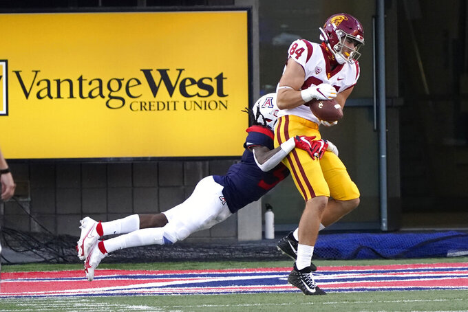 Southern California tight end Erik Krommenhoek (84) scores a touchdown against Arizona defensive back Jarrius Wallace (3) during the second half of an NCAA college football game Saturday, Nov. 14, 2020, in Tucson, Ariz. Southern California won 34-30. (AP Photo/Rick Scuteri)