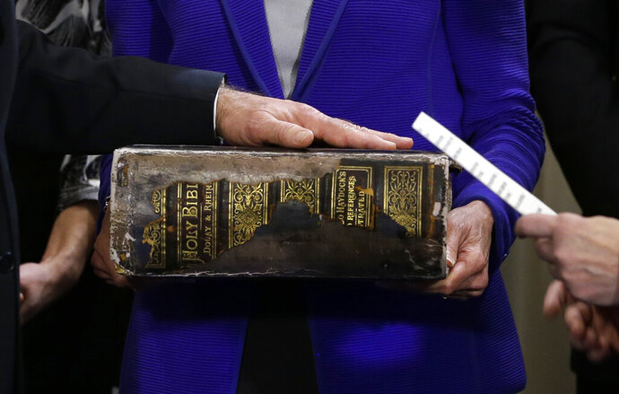 """FILE - In this Sunday, Jan. 20, 2013 file photo, Vice President Joe Biden, left, places his hand on the Biden family Bible held by his wife, Jill Biden, center, as he takes the oath of office from Supreme Court Justice Sonia Sotomayor, right, during an official ceremony at the Naval Observatory in Washington. While many presidents have used Bibles for their inaugurations, the Constitution does not require the use of a specific text and specifies only the wording of president's oath. That wording also doesn't include the phrase """"so help me God,"""" but every modern president has appended it to their oaths and most have chosen symbolically resonant Bibles for their inaugurations. (AP Photo/Carolyn Kaster)"""