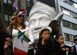 FILE - In this Oct. 12, 2015, file photo, participants in New York's Columbus Day Parade ride a float with a large bust of Columbus. The image and story Christopher Columbus, the 15th Century navigator who began European incursions into the Americas, have changed in the U.S. over decades. (AP Photo/Seth Wenig)