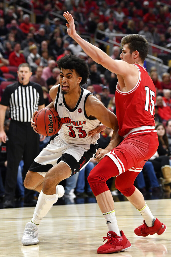 Louisville forward Jordan Nwora (33) works around Miami (Ohio) guard Milos Jovic (15) during the second half of an NCAA college basketball game in Louisville, Ky., Wednesday, Dec. 18, 2019. Louisville won 70-46. (AP Photo/Timothy D. Easley)