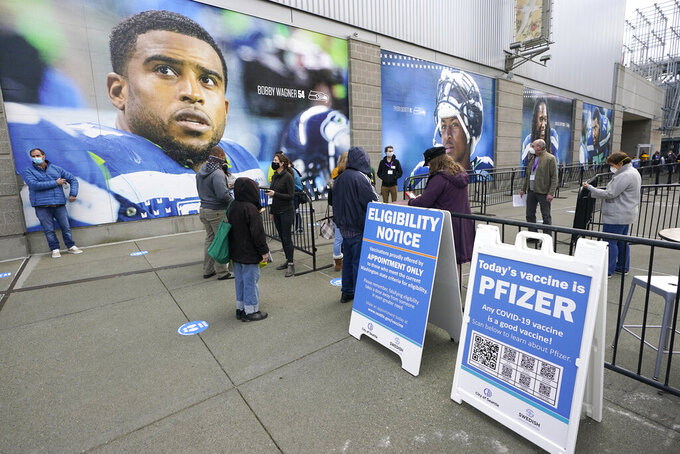 People line up in front of photos of Bobby Wagner, left, and other Seattle Seahawks players, Saturday, March 13, 2021, as they wait to get the first dose of the Pfizer COVID-19 vaccine on the first day of operations at a mass vaccination site at the Lumen Field Events Center in Seattle, which adjoins the field where the NFL football Seahawks and the MLS soccer Seattle Sounders play their games. The site, which is the largest civilian-run vaccination site in the country, will operate only a few days a week until city and county officials can get more doses of the vaccine. (AP Photo/Ted S. Warren)