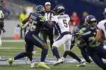 Denver Broncos quarterback Teddy Bridgewater (5) looks for a receiver while under pressure from Seattle Seahawks linebacker Jordyn Brooks (56) during the first half of an NFL preseason football game Saturday, Aug. 21, 2021, in Seattle. (AP Photo/Stephen Brashear)