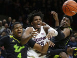 Connecticut's Josh Carlton, center, vies for the ball with South Florida's Michael Durr, left, and Alexis Yetna, right, during the second half of an NCAA college basketball game, Sunday, March 3, 2019, in Storrs, Conn. (AP Photo/Steven Senne)