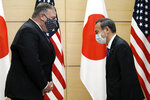 Japan's Prime Minister Yoshihide Suga, right, and U.S. Secretary of State Mike Pompeo, left, greet prior to their meeting at the prime minister's office Tuesday, Oct. 6, 2020, in Tokyo. Pompeo is in Japan to attend the four Indo-Pacific nations' foreign ministers meeting. (AP Photo/Eugene Hoshiko, Pool)