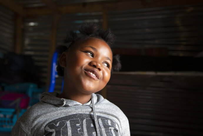 """Lilitha Jiphethu, 11, sings in her first language, Xhosa, inside her home in Orange Farm, South Africa, on Tuesday, April 28, 2020. """"I have a friend in Jesus. He is loving and he's not like any other friend. He is not deceitful. He is not ashamed of us. He is truthful, and He is love."""" (AP Photo/Denis Farrell)"""