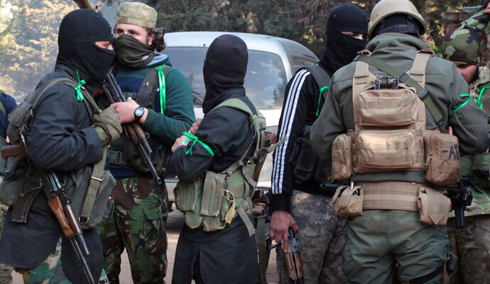 This photo released Feb. 24, 2018 by the al-Qaida-affiliated Ibaa News Agency, that is consistent with independent AP reporting, purports to show al-Qaida-linked fighters from Hayat Tahrir al-Sham or Levant Liberation Committee, in Idlib province, Syria. For the first time since its meteoric rise in 2012 amid the chaos of war, al-Qaida branch in Syria is on the retreat, battling rival insurgent groups north of the country and fighting for survival in a key foothold near the capital Damascus. (Ibaa News Agency, via AP)