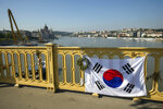FILE - In this Saturday, June 8, 2019 file photo, a Korean flag adorns the rail of Margaret Bridge, the scene of the deadly boat accident in Budapest, Hungary. Hungarian police say that the deceased captain of the tour boat which sank after colliding with a river cruise ship on the Danube River was not to blame for the deadly incident. Twenty-eight people, mostly South Korean tourists, aboard the Hableany (Mermaid) sightseeing boat died after their vessel collided with the Viking Sigyn river cruise ship on May 29, 2019. The remains of a South Korean tourist have yet to be recovered (Balazs Mohai/MTI via AP, file)