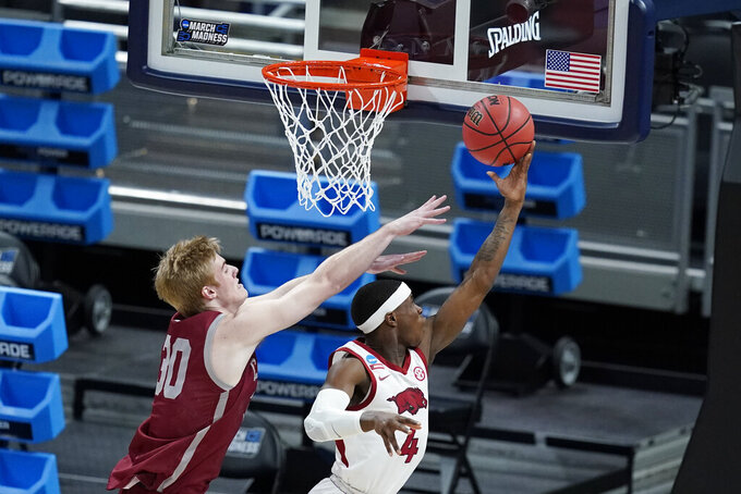 Arkansas' Davonte Davis (4) puts up a shot against Colgate's Sam Thomson (30) during the first half of a first round game at Bankers Life Fieldhouse in the NCAA men's college basketball tournament, Friday, March 19, 2021, in Indianapolis. (AP Photo/Darron Cummings)