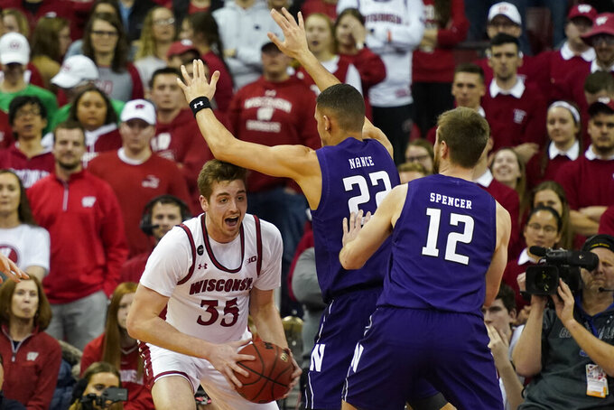 Northwestern's Pete Nance (22) and Pat Spencer (12) guard Wisconsin's Nate Reuvers (35) during the first half of an NCAA college basketball game Wednesday, March 4, 2020, in Madison, Wis. (AP Photo/Andy Manis)