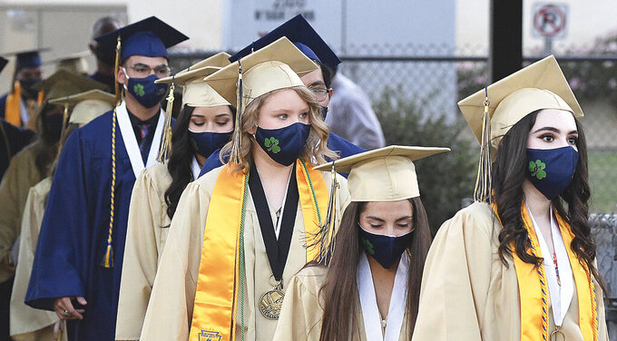 Members of the Class of 2020, all wearing face masks, file into a stadium at Yuma Catholic High School for the graduation ceremony Wednesday, June 10, 2020, in Yuma, Ariz., during the coronavirus pandemic. (Randy Hoeft/The Yuma Sun via AP)