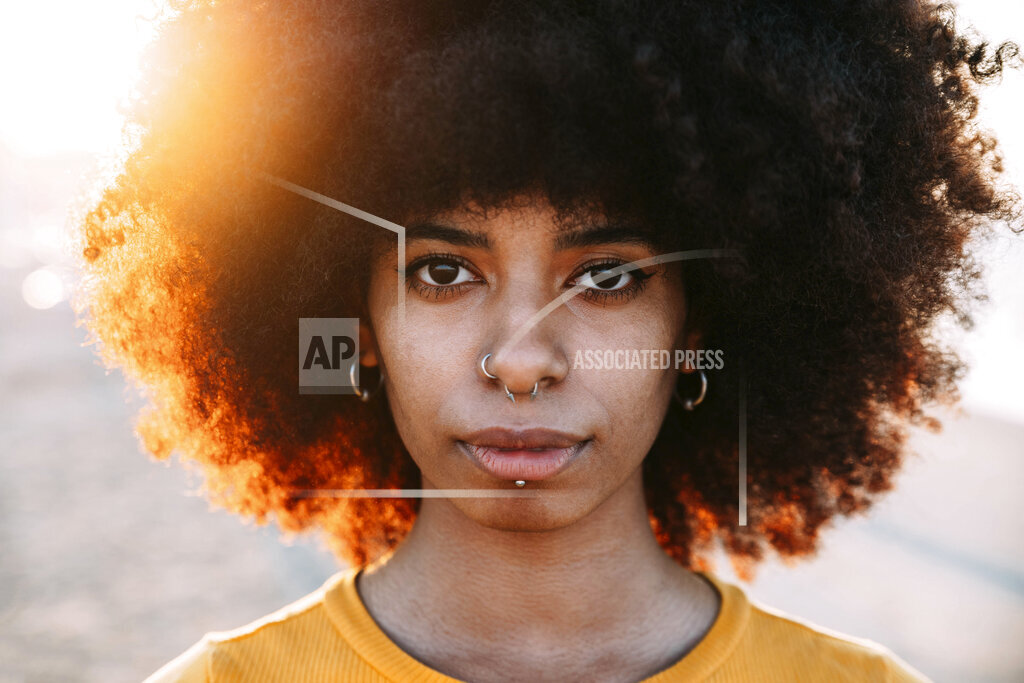 Afro woman with pierced nose during sunset