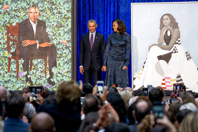 FILE - In this Feb. 12, 2018, file photo, former President Barack Obama and former first lady Michelle Obama stand on stage together as their official portraits are unveiled at a ceremony at the Smithsonian's National Portrait Gallery in Washington. The portraits will begin a five-city national tour in Chicago in June 2021. The Art Institute of Chicago will host the portraits from June 18, 2021, to Aug. 15, 2021, the gallery announced Thursday, Jan. 23, 2020. (AP Photo/Andrew Harnik, File)