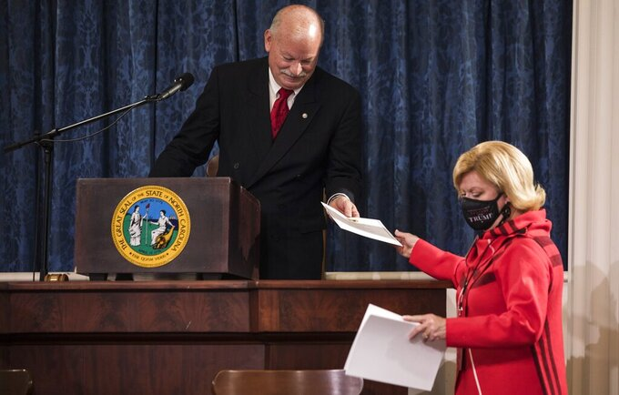 Mark Delk, president of the Electoral College, hands president teller Susan Mills electoral ballots to be shared with electors in the house chambers of the Old State Capitol building in Raleigh, N.C., on Monday, Dec. 14, 2020. (Julia Wall/The News & Observer via AP)