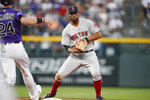 Boston Red Sox shortstop Xander Bogaerts, back, fields the throw from second baseman Brock Holt to force out Colorado Rockies' Ryan McMahon at second base on a ground ball hit by Yonathan Daza in the second inning of a baseball game Wednesday, Aug. 28, 2019, in Denver. (AP Photo/David Zalubowski)