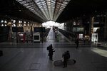 Commuters wait next to empty platforms at Gare du Nord Station, in Paris, Tuesday, Dec. 10, 2019. Only about a fifth of French trains ran normally Tuesday, frustrating tourists finding empty train stations, and most Paris subways were at a halt. French airport workers, teachers and others joined nationwide strikes Tuesday as unions cranked up pressure on the government to scrap changes to the national retirement system. (AP Photo/Francois Mori)