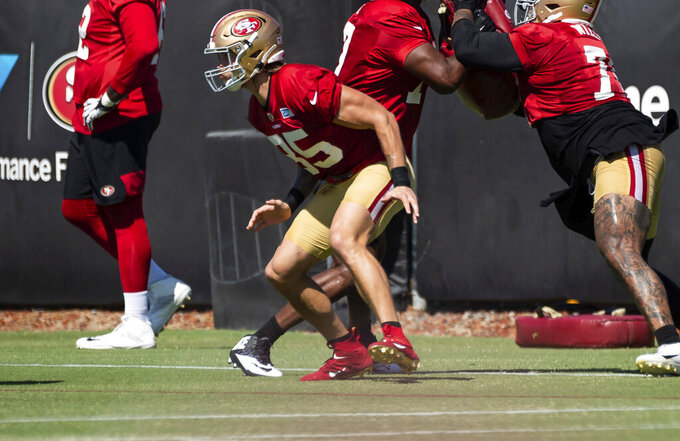 San Francisco 49ers tight end George Kittle (85), left, gets low for a block during a drill at the NFL Training Camp practice Saturday, Aug. 15, 2020, at the SAP Performance Facility in Santa Clara, Calif. (Xavier Mascarenas/The Sacramento Bee via AP)