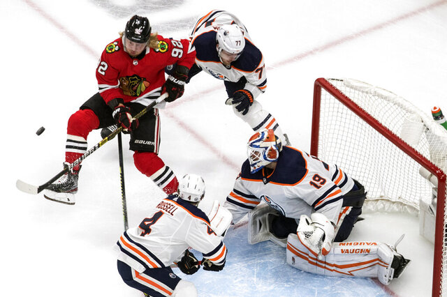 Edmonton Oilers goalie Mikko Koskinen (19) makes the save as Chicago Blackhawks' Alex Nylander (92) and Oilers' Oscar Klefbom (77) battle for the puck during the third period of an NHL hockey playoff game Friday, Aug. 7, 2020, in Edmonton, Alberta. (Jason Franson/Canadian Press via AP)