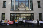 Protesters hold banners outside Westminster Magistrates Court in London, where Julian Assange is due to appear, Monday, Jan. 13, 2020. Protesters will be insisting that Assange should not be extradited to the US for his reporting of the Iraq and Afghanistan war. They insist he will not face a fair trial in the United States where the charges against him could result in imprisonment for 175 years. Assange will be transported from Belmarsh high-security prison. (AP Photo/Kirsty Wigglesworth)