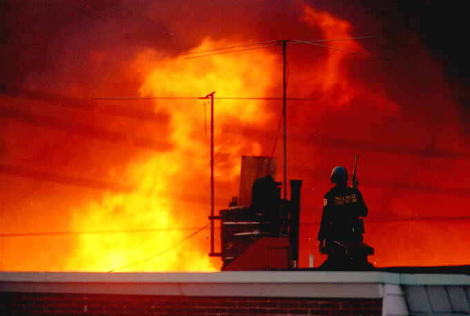 FILE - In this May, 1985 file photo, a Philadelphia policeman is seen on a rooftop as flames rise from a row of burning homes beyond, in Philadelphia. The fire started when police dropped a bomb onto the house of the militant group MOVE, on May 13, 1985 and fire spread throughout the area. A day after Philadelphia's health commissioner was forced to resign over the cremation of partial remains thought to belong to victims of a 1985 bombing of the headquarters of a Black organization, the city now says those victims' remains were never destroyed. City officials told the victims' family Friday, May 14, 2021 that a subordinate had disobeyed Health Commissioner Thomas Farley's 2017 order to dispose of the remains. (AP Photo/George Widman, File)