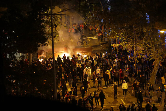 Demonstrators stand by a burning barricade in Barcelona, Spain, Saturday, Oct. 19, 2019. Barcelona and the rest of the restive Spanish region of Catalonia are reeling from five straight days of violent protests for the sentencing of 12 separatist leaders to lengthy prison sentences.The riots have broken out at nightfall following huge peaceful protests each day since Monday's Supreme Court verdict. (AP Photo/Manu Fernandez)