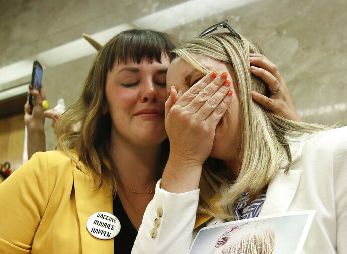 Jessica Purciful, left, and Angela Hicks, who both opposed a measure that would give public health officials oversight of doctors that may be giving fraudulent medical exemptions from vaccinations, console each other after Bill SB276 was approved by the Assembly Health Committee at the Capitol in Sacramento, Calif., Thursday, June 20, 2019. (AP Photo/Rich Pedroncelli)