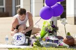 Troy Osborne, 17, a member of the Elgin football team, writes a message at a memorial for two slain students at Elgin High School on Monday April 19, 2021. Police in Texas say a former sheriff's deputy accused of killing his wife, teenager daughter and another man in a weekend shooting has been booked on a capital murder charge. Authorities on Monday arrested 41-year-old Stephen Broderick following an overnight manhunt. Manor Police Chief Ryan Phipps says Broderick was arrested without incident along a rural road in an Austin suburb. (Jay Janner/Austin American-Statesman via AP)
