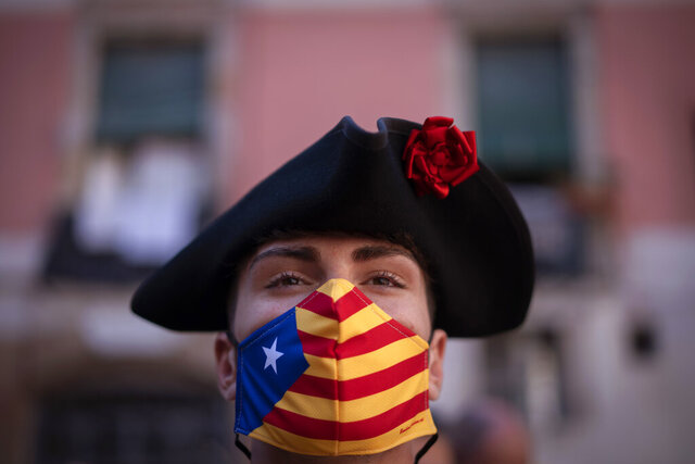 A man wearing a face mask decorated with the independent flag looks on during the Catalan National Day in Barcelona, Spain, Friday, Sept. 11, 2020. Thousands of Catalans in favour of gaining independence from the rest of Spain are expected to rally Friday afternoon in commemoration of