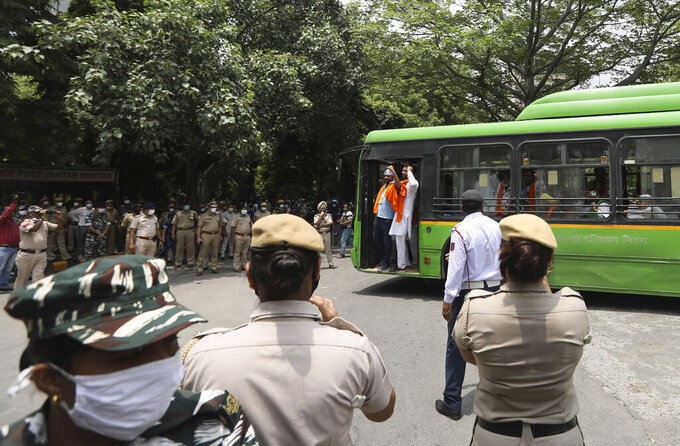 Indian policemen stand guard as farmers arrive at a protest site to hold a mock farmer's parliament in New Delhi, India, Thursday, July 22, 2021. More than 200 farmers on Thursday began a protest near India's Parliament to mark eight months of their agitation against new agricultural laws that they say will devastate their income. (AP Photo/Manish Swarup)