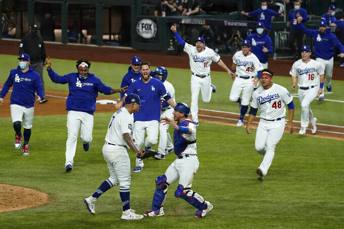 FILE - In this Oct. 27, 2020, file photo, Los Angeles Dodgers celebrate after defeating the Tampa Bay Rays 3-1 in in Game 6 to win baseball's World Series in Arlington, Texas. (AP Photo/Tony Gutierrez, File)