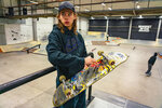 In this Jan. 16, 2020 photo, skateboarder Oskar Rozenberg checks his board, at Bryggeriet Malmo Skatepark in Malmo, Sweden. Skateboarding is coming to the Olympics for the first time at this year's Tokyo Games and a Swedish star known for his creativity and spontaneous routines might be the breakout star. Oskar Rozenberg is the reigning two-time skateboarding world champion from the Vans Park Series Pro Tour. (AP Photo/David Keyton)